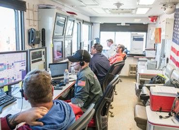 Committed control room personnel monitor pipeline flow